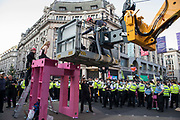 Police officers remove an Extinction Rebellion activist who had taken part in a pink roadblock of Oxford Circus by women and FINT-identifying environmental activists during the third day of Impossible Rebellion protests on 25th August 2021 in London, United Kingdom. Extinction Rebellion are calling on the UK government to cease all new fossil fuel investment with immediate effect.