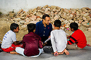 11th March 2014, Shakarpur, New Delhi, India. Anil Kumar Lal a volunteer teacher teaches children at a makeshift school under a metro bridge near the Yamuna Bank Metro station in Shakarpur, New Delhi, India on the 11th March 2014<br /> <br /> Rajesh Kumar Sharma (born 01/02/1970), started this makeshift school in 2011. Six mornings a week he teaches underprivileged children for three hours while his younger brother replaces him at his general store in Shakarpur. His students are children of labourers, rickshaw-pullers and farm workers. This is the 3rd site he has used to teach under privileged children in the city, he began in 1997. <br /> <br /> PHOTOGRAPH BY AND COPYRIGHT OF SIMON DE TREY-WHITE<br /> + 91 98103 99809<br /> email: simon@simondetreywhite.com<br /> photographer in delhi<br /> journalist