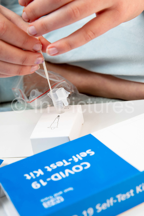 A secondary school pupil puts the swab into the extraction tube for a COVID-19 Lateral Flow test. Lateral Flow Device LFD kits were given to all secondary school pupils in England so they can test themselves twice a week at home on the 21st March 2021 in Folkestone, United Kingdom.