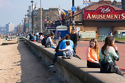 Portobello, Scotland, UK. 25 April 2020. Views of people outdoors on Saturday afternoon on the beach and promenade at Portobello, Edinburgh. Good weather has brought more people outdoors walking and cycling. The beach appears busy with possibly a breakdown in social distancing happening later in the afternoon. Seawall busy with people sitting outside. Iain Masterton/Alamy Live News
