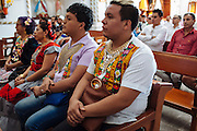 """Angelo Martinez Linares, 24, during a mass in Juchitán, Mexico.<br /> <br /> In Juchitán in the southern state of Oaxaca, Mexico, the world is not divided simply into gay and straight, the locals make room for a third category, whom they call """"muxes"""".<br /> <br /> Muxes are men who consider themselves women and live in a socially sanctioned netherworld between the two genders. """"Muxe"""" is a Zapotec word derived from the Spanish """"mujer"""" or woman; it is reserved for males who, from boyhood, have felt themselves drawn to living as a woman, anticipating roles set out for them by the community.<br /> <br /> They are considered hard workers that will forever stay by their mothers side, taking care for their families operating as mothers without children of their own.<br /> <br /> Not all muxes express they identities the same way. Some dress as women and take hormones to change their bodies. Others favor male clothes. What they share is that the community accepts them."""