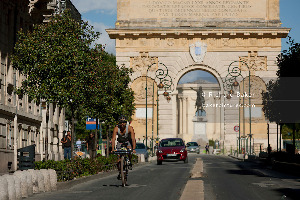 Local cyclist on the Rue Foch in front of the 17th century Arc de Triomphe in Montpellier, south of France.