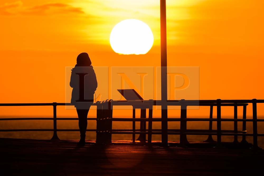 ©Licensed to London News Pictures.<br /> Aberystwyth UK,  25/03/2019. <br /> The spectacular sunset silhouettes a person  on the seafront in Aberystwyth at the end of a lovely spring day of clear unbroken blue skies, as high pressure dominates the weather over much of the UK for the coming days. <br /> photo Keith Morris/LNP