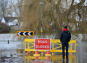 © Licensed to London News Pictures. 29/12/2012. Laleham, UK. A man stands at a road closed sign and looks at the flooded River Thames in Laleham.  Flooding along the River Thames today 29th December 2012.Forecasters say the UK can expect heavy rain and winds the coming days. Photo credit : Stephen Simpson/LNP