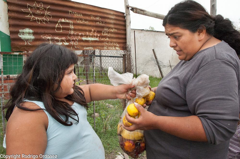 Verónica, 8 (left), hands some lemons to her aunt Mónica Jiménez.