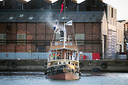 """© Licensed to London News Pictures. 04/05/2016. Birkenhead UK. Picture shows the Daniel Adamson leaving the Camel Laird ship yard in Birkenhead & making it's first public appearance for 30 years traveling across the Mersey last night to Canning Dock in Liverpool. The Daniel Adamson steam boat has been bought back to operational service after a £5M restoration. The coal fired steam tug is the last surviving steam powered tug built on the Mersey and is believed to be the oldest operational Mersey built ship in the world. The """"Danny"""" (originally named the Ralph Brocklebank) was built at Camel Laird ship yard in Birkenhead & launched in 1903. She worked the canal's & carried passengers across the Mersey & during WW1 had a stint working for the Royal Navy in Liverpool. The """"Danny"""" was refitted in the 30's in an art deco style. Withdrawn from service in 1984 by 2014 she was due for scrapping until Mersey tug skipper Dan Cross bought her for £1 and the campaign to save her was underway. Photo credit: Andrew McCaren/LNP ** More information available here http://tinyurl.com/jsucxaq **"""