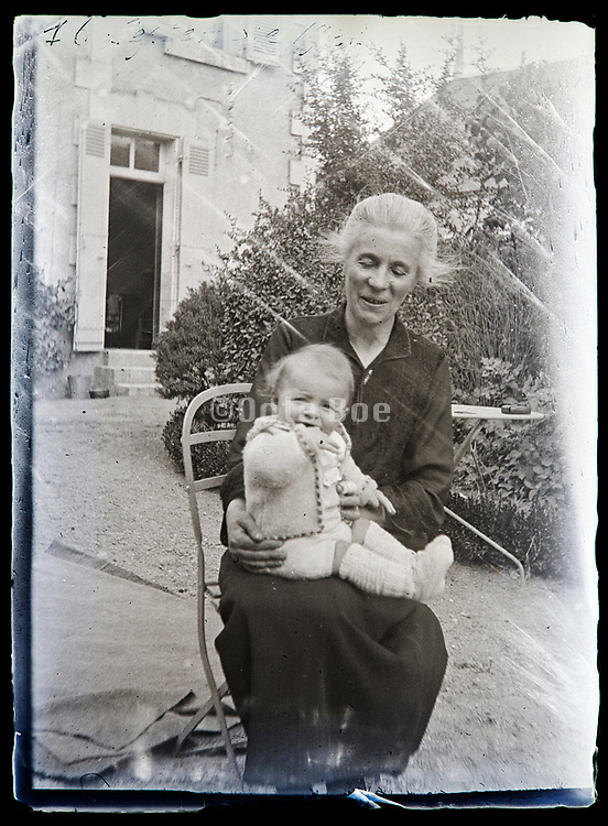happy grandmother holding a little baby toddler on her lap France 1920s