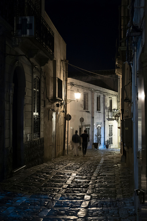Lamplight on stone cobbles at night and tourist couple strolling along cobbled alleyway in Erice, Sicily, Italy