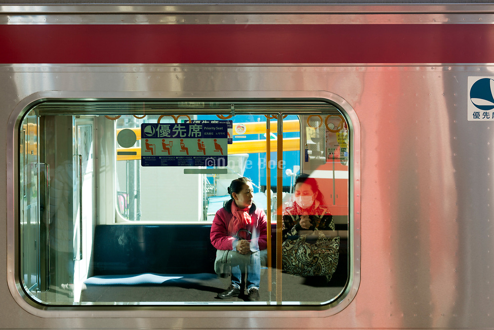 two women sitting in a train wagon with priority seat sign on the window Japan