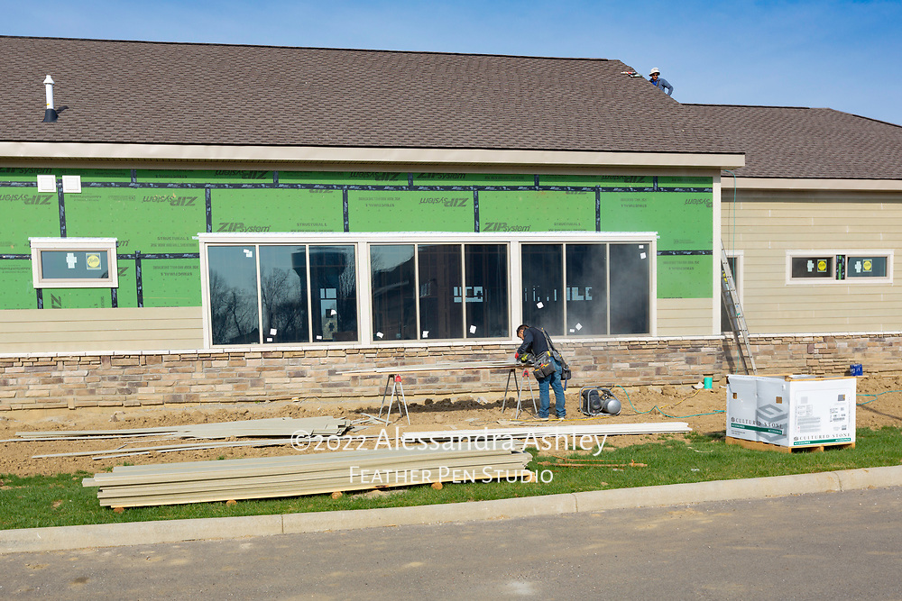 Siding installation in progress at building site of new physical therapy and wellness center.