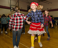 """Bandanas, pigtails and plaid on the dance floor as Janney Halperin """"swings her partner"""" Abby Smith during Inter Lakes Elementary School's annual Square Dance on Thursday afternoon.  (Karen Bobotas/for the Laconia Daily Sun)"""