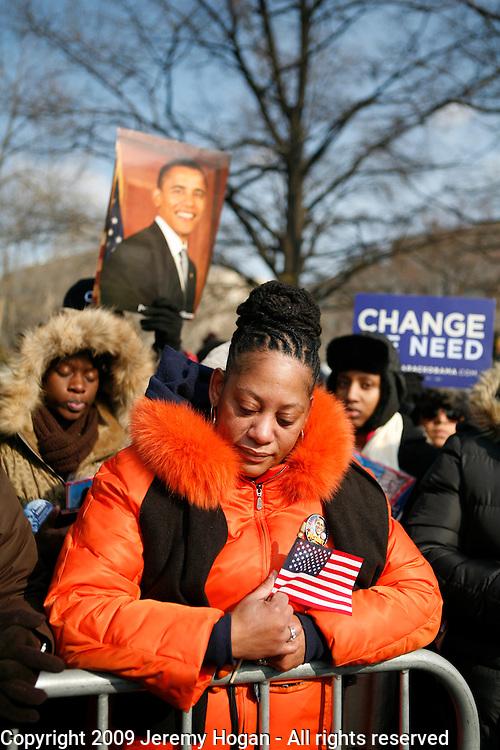 Linda Walker, of Bayshore, New York, (orange jacket) contemplates as Barack Obama is sworn in as president of the United States.