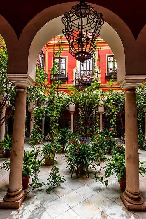 A courtyard patio in the Santa Cruz neighborhood (the former Jewish Quarter (Juderia) in the Medieval  quarter, Seville, Andalusia, Spain.