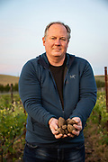 Portrait of Mike Martin owner of The Walls winery in The Rocks AVA holding a handful of vineyard cobbles.