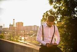Businessman working on digital tablet at sunset, Munich, Bavaria, Germany