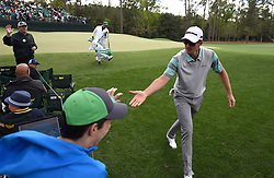 Justin Rose, right, slaps hands with a fan along the 14th green during first round action of the 2017 Masters Tournament at Augusta National Golf Club on Thursday, April 6, 2017 in Augusta, Ga. Rose finished the round at -1. (Photo by Jeff Siner/Charlotte Observer/TNS) *** Please Use Credit from Credit Field ***