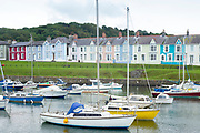Pleasure boats - powerboats and yachts in harbour - bright painted harbourside housing in Aberaeron, Pembrokeshire, Wales, UK