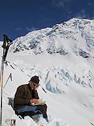A backcountry skier pauses for a bit of reading, Chugach Mountains, Alaska.
