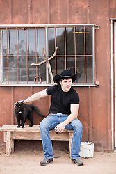 cowboy sitting on a bench with a cat