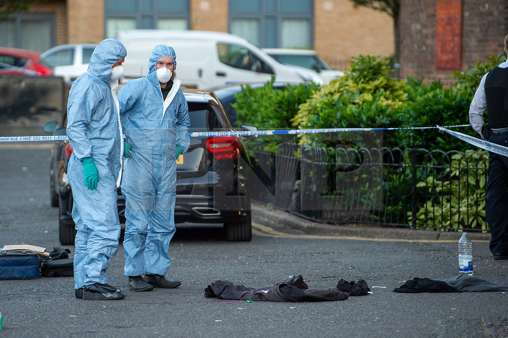 © Licensed to London News Pictures. 20/07/2020. London, UK. Forensic investigators look over clothes lying next to a pool of blood at the crime scene as police launch investigation after two people were stabbed in Tower Hamlets. Photo credit: Peter Manning/LNP