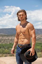 muscular tan cowboy outdoors on a mountain range