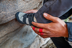 Guide Jacob Garza showing Sarah Hepola how to plant foot while climbing, Hueco Tanks State Park & Historic Site, El Paso, Texas. USA.