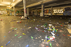 © Licensed to London News Pictures. 23/12/2013. London, UK. Graffiti and litter left inside the warehouse in Pennington Street, East London, where an illegal 'Stanta Stomp' rave took place on the night of 21 December and two people were stabbed and a police officer injured.. Photo credit : Vickie Flores/LNP