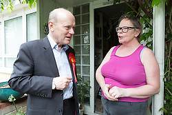 © Licensed to London News Pictures. 23/05/2015. London, UK. Labour Party candidate for Tower Hamlets Mayor, John Biggs speaks to a woman during canvassing on the Isle of Dogs in Tower Hamlets, east London. The Tower Hamlets Mayoral election will be re-run on 11th June after a High Court election petition found the previously elected mayor, Lutfur Rahman guilty of corrupt and illegal practices. Photo credit : Vickie Flores/LNP