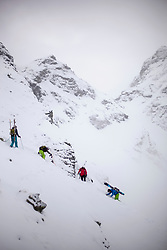 Skitour group climbing snow covered mountain