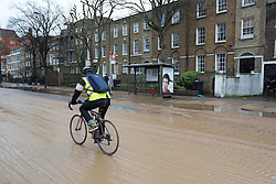 © Licensed to London News Pictures. 28/02/2014. London, UK. Commuters on bicycles cycle through mud and sediment after a burst watermain on Clapham Road in Kennington, London today (28/02/2014). The watermain, which burst yesterday evening flooding a section of Clapham Road - a major in and out of the city - with thousands of litres of water, has today caused widespread disruption to traffic. Photo credit: Matt Cetti-Roberts/LNP
