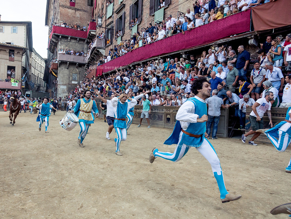 Italy, Siena, the Palio: the festivities begins straight away, the  excited people of the contrada jump into the the race track and  rushed into the area also before the moment of its goal and made a big chaos and run to recieve the Palio banner and with it they go to the Duomo. the Onda is the winner