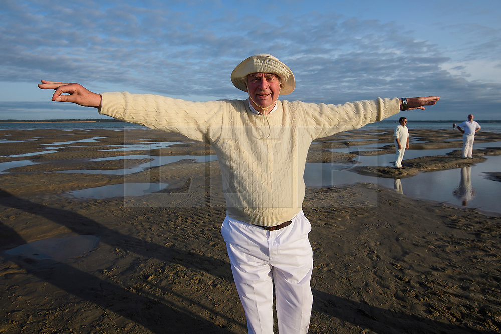 © Licensed to London News Pictures. 24/08/2017. Solent, UK. The umpire signals for a score of six. Teams take part in the Brambles Bank Cricket Match in the middle of The Solent strait on August 24, 2017. The annual cricket match between the Royal Southern Yacht Club and The Island Sailing Club, takes place on a sandbank which appears for 30 minutes at lowest tide. The game lasts until the tide returns. Photo credit: Ben Cawthra/LNP