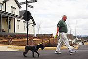 """HOOVER, AL – MARCH 1, 2016: Martin Ennis, 68, walking his dog Lucy in the Moss Rock Preserve neighborhood. """"I'm a conservative but not Republican,"""" Ennis said. """"The last 8 years the progressives have taken over everything. We've gotten away from the constitution in many ways. Politics is about choices, not ideals. So if it's between trump and Clinton, yeah, I'm gonna vote for Trump. I worry, but that's what I'll do. And I feel conflicted in that because I feel he is not the answer.""""<br /> <br /> On Super Tuesday, voters in the economically vibrant city of Hoover turned out to voice their support for a presidential candidate. Located in the Appalachian foothills, Hoover is the largest suburb of Birmingham and is home to several planned communities with idyllic neighborhoods tailored for the upper middle class. CREDIT: Bob Miller for The Wall Street Journal<br /> OLDCITIES"""