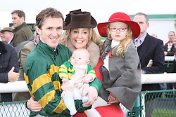 ©Licensed to London News Pictures. 07/11/2013<br /> Towcester Racecourse, Northamptonshire. AP McCoy wins the magic 4000 at Towcester Racecourse in the 3:10 Weatherbys Novice hurdle race with wife Channelle and children Eve and Archie.<br /> Photo credit: Steven Prouse/ LNP