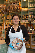 A friendly female waitress at the Italian delicatessen, Lina Stores, on 19th October 2015 in London, United Kingdom. Family-run Italian deli serving homemade pasta, cheese, cured meats, groceries and fresh coffee in the heart of Soho.