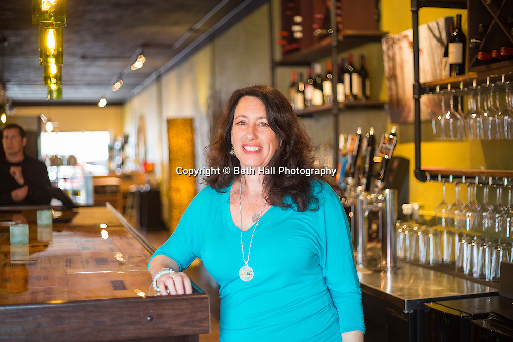 Laura Brown, owner of Ramo D'Olivo, a wine bar and olive oil store, stands near the bar on Friday, April 24, 2015, in Bentonville, Ark.<br /> <br /> Photo by Beth Hall