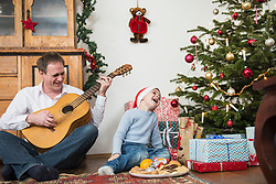 Father playing guitar and son singing