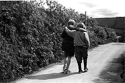 Young boy and girl walking along a country path with their arms around each other,