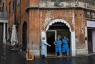 Women take a work break outside a shop in Rome, Italy