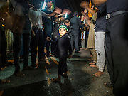 04 NOVEMBER 2014 - YANGON, MYANMAR: A Burmese boy stands in between lines of mine who are pounding their chests and chanting prays to Hussein ibn Ali on Ashura in Yangon. Ashura commemorates the death of Hussein ibn Ali, the grandson of the Prophet Muhammed, in the 7th century. Hussein ibn Ali is considered by Shia Muslims to be the third imam and the rightful successor of Muhammed. He was killed at the Battle of Karbala in 610 CE on the 10th day of Muharram, the first month of the Islamic calendar. According to Myanmar government statistics, only about 4% of the population is Muslim. Many Muslims have fled Myanmar in recent years because of violence directed against Burmese Muslims by Buddhist nationalists.    PHOTO BY JACK KURTZ