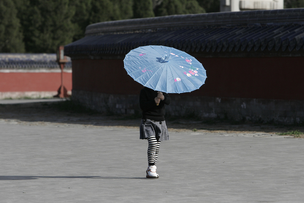 A young girl hides from the sun while walking around the Circular Mound Altar at Temple of Heaven. The Temple of Heaven in south east Beijing, China was built in 1420 A.D. as a place for the 'Son of Heaven', the Emperor, to offer sacrifice to Heaven.  Temple of Heaven is larger than the Forbidden City with an area of over 2,000,000 meters.