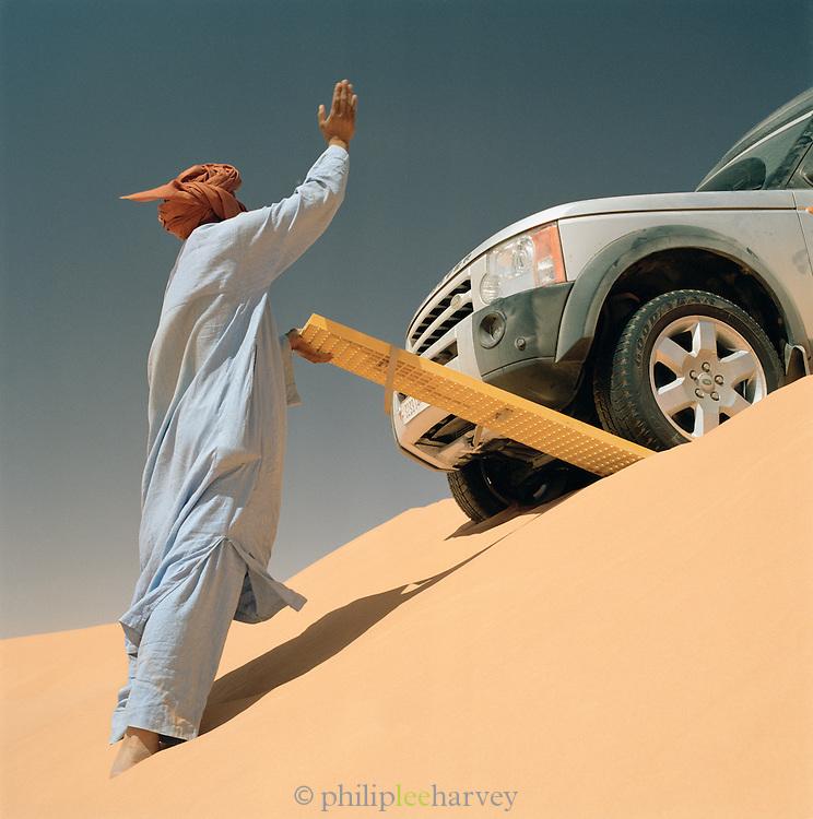 Tuareg guide directs driver of 4x4 onto a sand ladder, Sahara desert, Libya