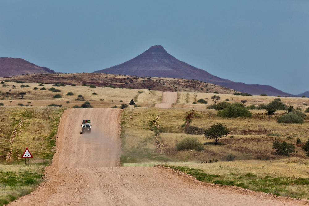 A 4x4 Landcruiser drives into the distance on a dirt road in the Palmwag consession in Namibia.