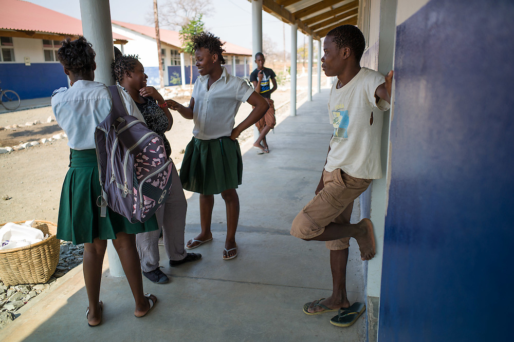 Students joke around during lunch break in the newly built boarding school. It is difficult for families to send their children to school due to the lack of income  because of missing infrastructure. Most students come from other towns and villages and stay in the school during the week. <br /> <br /> Mozambique has attracted two of the world's largest mining companies – Brazil's Companhia Vale do Rio Doce (Vale) and the Anglo-Australian multinational Rio Tinto – to extract coal from the huge fields in Tete province. In an effort of exploitation, over 700 families from the villages of Chipanga, Mitete, Malabue-Gombe and Bagamoyo were resettled to Cateme village, a Vale resettlement compound. Vale deliberately divided the communities in two with employed villagers moving to 25 de Setembro since it is closer to Moatize and the coal mine. The unemployed were resettled to Cateme, 40 km from the original town. While the most immediate problem of the community is the enormous distance to Moatize, their old habitat, they also suffer from unproductive farmland which can only be reached via a two hour walk, no access to markets and infrastructure and poorly constructed houses not fitted to the people's needs with temperatures inside reaching as high as 55° C due to the construction with tin clad roofs.