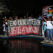 Protesters chant and hold signs, prior to the George Zimmerman murder verdict at the Seminole County Courthouse on Saturday, July 13, 2013, in Sanford, Florida.  Zimmerman had been charged for the 2012 shooting death of Trayvon Martin and was found not guilty by a jury of six women. The protests on the grounds ended peacefully after the verdict was read. (AP Photo/Alex Menendez)