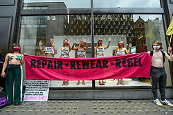 "© Licensed to London News Pictures. 09/09/2020. LONDON, UK.  Activists from Extinction Rebellion (XR) stage a ""Guerilla Repair"" pop-up outside the H&M store on Oxford Street to protest against the environmental and human effects of fast fashion and disposable fashion. Some are have glued their hands to the inside of the shop window. Photo credit: Stephen Chung/LNP"