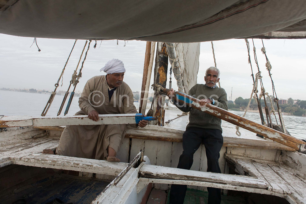 Two crewmen of a felucca row their boat during a drop in wind while sailing on the River Nile at Luxor, Nile Valley, Egypt. Feluccas are ancient Egyptian sail boats which were used in ancient times as a primary mode of transport and are the only type of boat that is still used extensively in the country. Plying this great African river is a cheap fare state-run ferry used by commuters and locals but these sailing boats serve tourists and therefore are the many victims of the tourism downturn. According to the country's Ministry of Tourism, European visitors to Egypt is down by up to 80% in 2016 from the suspension of flights after the downing of the Russian airliner in Oct 2015. Euro-tourism accounts for 27% of the total flow and in total, tourism accounts for 11.3% of Egypt's GDP.