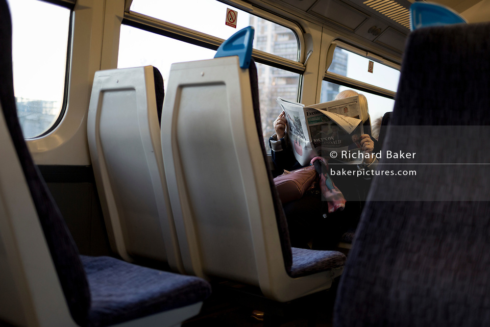 Seen from across the aisle of a train carriage, a waldy reads a copy of the Evening Standard newspaper with a headlne about the NATO's 70th anniversary summit taking place in Watford, in London, England, on 4th December 2019.