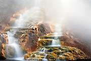 Water from the Grand Prismatic Spring flows into the Firehole River, Midway Getser Basin, Yellowstone National Park, Wyoming.