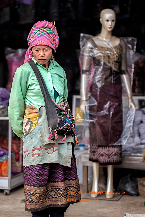 Mirrored Fashion: A tribal woman stands in front of a shop, were a mannequin is wearing a dress that is very similar to the one she has chosen to wear to this morning's market, Louang Namtha Laos.